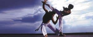 dois atletas jogando com calça de capoeira feita de helanca